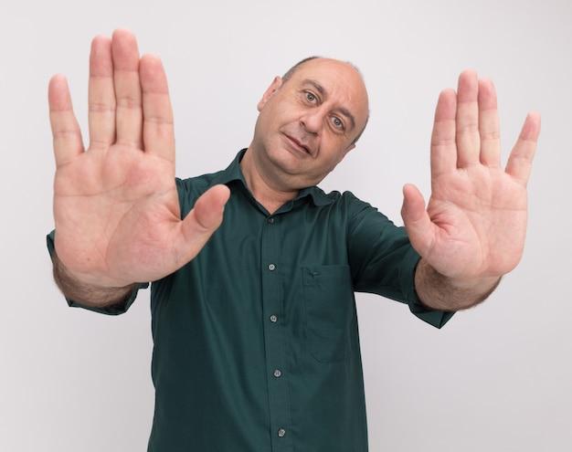 白い壁に停止のジェスチャーを示す緑の t シャツを着た、喜んで頭を傾ける中年男性