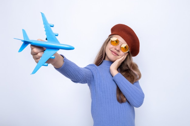 Довольно наклонив голову, положив руку на щеку, красивая маленькая девочка в очках с шляпой, протягивая игрушечный самолетик на белой стене