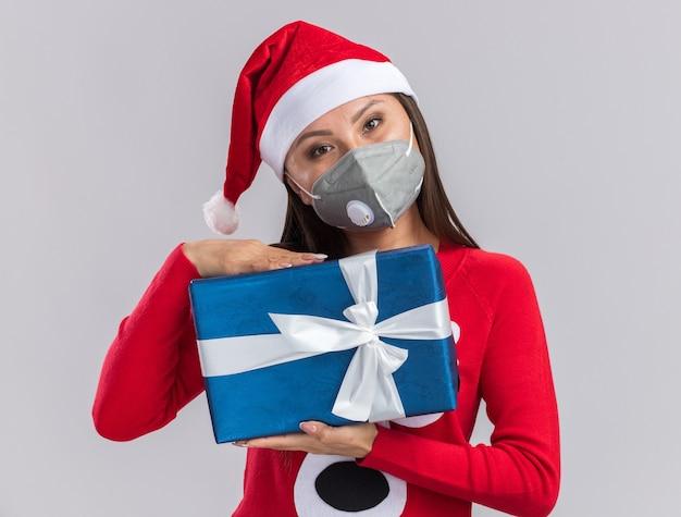 Довольно наклонив голову молодая азиатская девушка в новогодней шапке со свитером и медицинской маской держит подарочную коробку на белом фоне