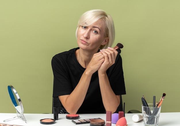 喜んで傾斜頭の若い美しい少女は、オリーブグリーンの壁に分離された化粧ブラシを保持している化粧ツールでテーブルに座っています