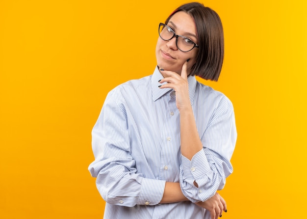 Pleased tilting head young beautiful girl wearing glasses putting finger on cheek