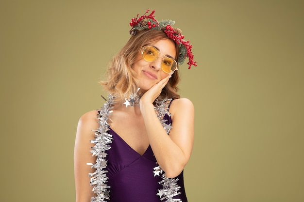 Pleased tilting head young beautiful girl wearing purple dress and glasses with wreath and garland on neck putting hand on cheek isolated on olive green background