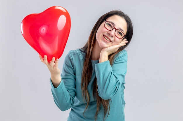 Pleased tilting head young girl on valentines day holding heart balloon putting hand on cheek isolated on white background