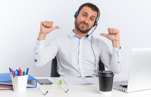 Soddisfatto testa inclinata giovane operatore di call center maschio che indossa l'auricolare seduto al tavolo con strumenti per ufficio punta a se stesso isolato su muro bianco
