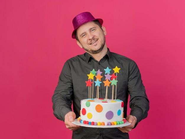 Довольный наклонив голову молодой тусовщик в розовой шляпе держит торт, изолированный на розовом