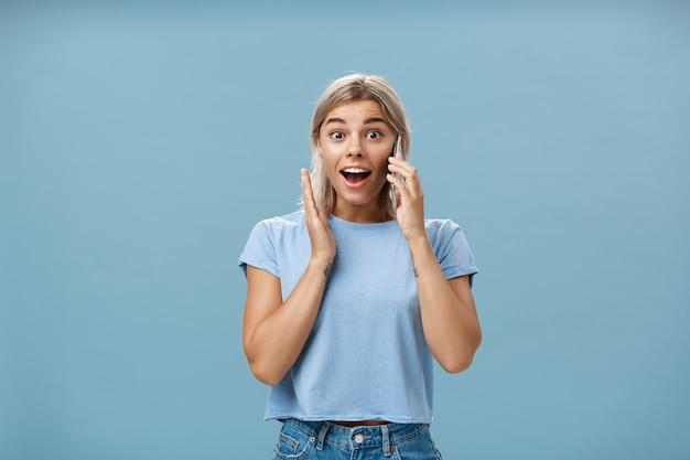 가장 친한 친구가 해외에서 전화하는 것을 듣고 기쁩니다. 얼굴에 귀 근처에 스마트 폰을 들고 놀랍게도 유행 티셔츠 여는 입에 놀란 만족 된 매력적인 금발 여성의 초상화