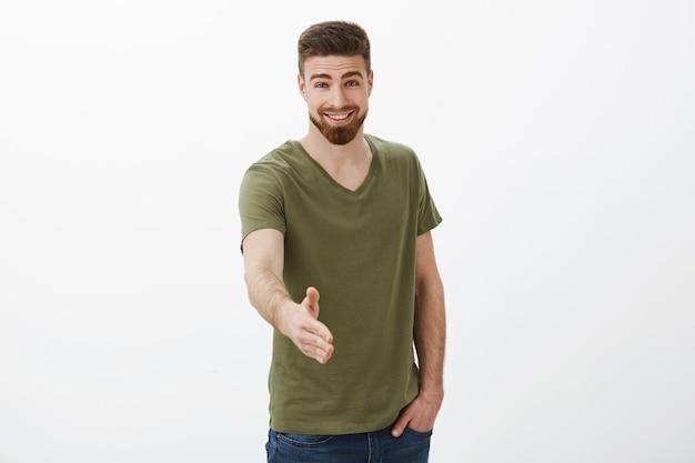 お会いできて嬉しいです。カリスマ的なハンサムで運動の若い男の肖像ビジネスを開始するあなたに握手で手を伸ばし、フレンドリーで挨拶、挨拶、挨拶を笑顔