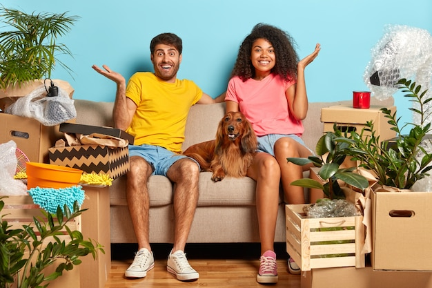 Pleased unaware married couple on sofa with dog surrounded with cardboard boxes