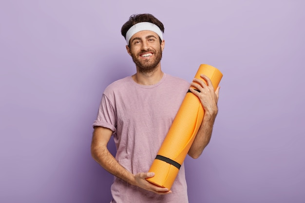 Pleased unshaven male holds rolled fitness mat, satisfied after yoga class