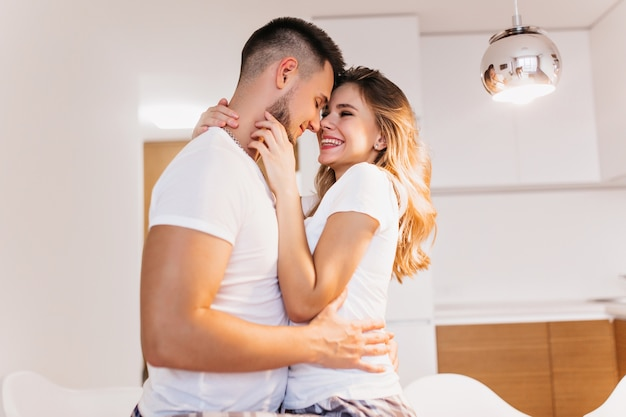 Uomo bianco soddisfatto in posa sognante con la moglie. tiro al coperto di giovani caucasici che esprimono amore.