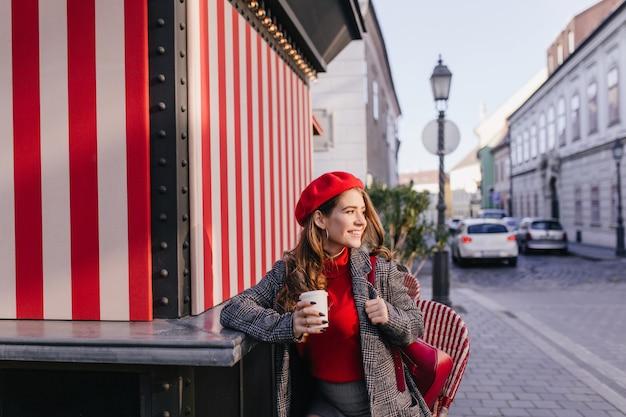路上でコーヒーを飲み、かわいい笑顔で周りを見回して喜んでいる白人女性