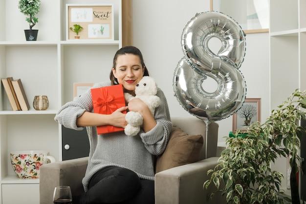 행복한 여성의 날에 아름다운 소녀가 거실의 안락의자에 앉아 있는 테디베어와 함께 선물을 들고 눈을 감고 기쁘게 생각합니다.