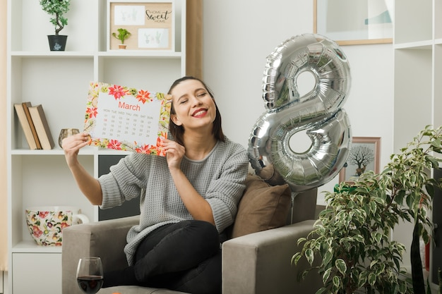 Felice con gli occhi chiusi bella donna in una felice giornata delle donne che tiene il calendario seduto sulla poltrona in soggiorno