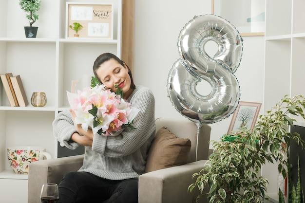 リビングルームの肘掛け椅子に座って花束を保持している幸せな女性の日に目を閉じて美しい女性に満足