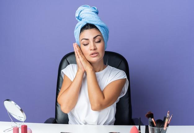 눈을 감고 기뻐하는 아름다운 여성은 화장 도구로 머리를 수건으로 감싼 채 테이블에 앉아 수면 제스처를 보여줍니다