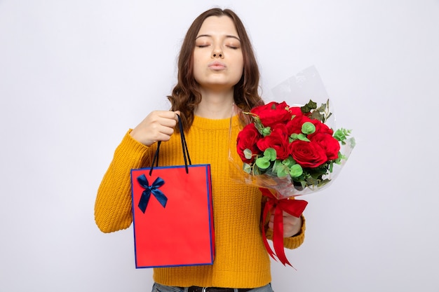 Pleased with closed eyes beautiful young girl on happy woman's day holding gift bag with bouquet isolated on white wall