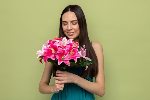 올리브 녹색 벽에 격리된 꽃다발을 들고 있는 아름다운 소녀가 눈을 감고 기뻐합니다.