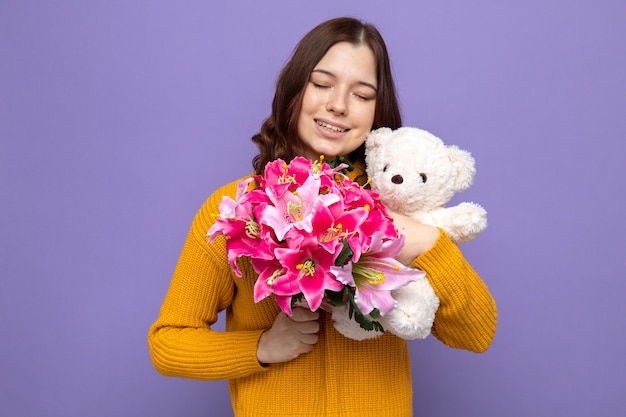 테디 베어와 함께 꽃다발을 들고 눈을 감고 기쁘게 생각하는 아름다운 어린 소녀