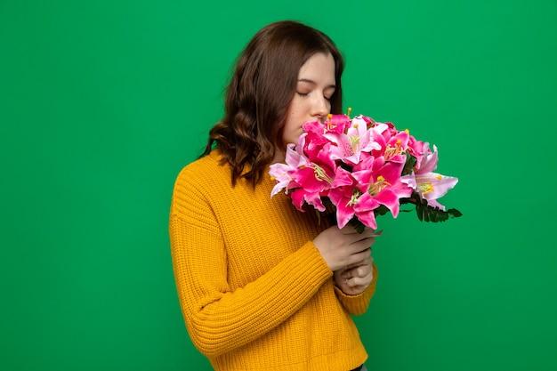 Soddisfatto degli occhi chiusi bella ragazza che tiene e annusa il bouquet