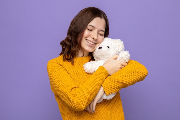 Pleased with closed eyes beautiful young girl holding teddy bear