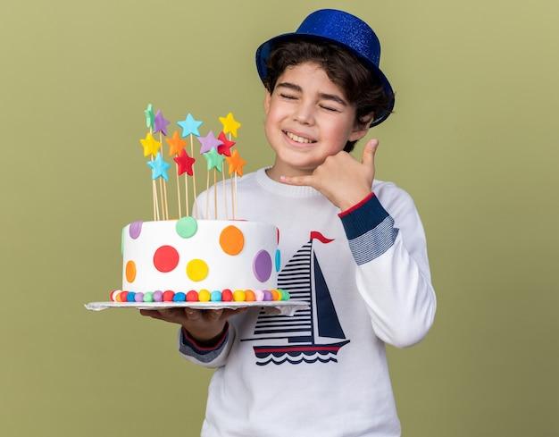 전화 제스처를 보여주는 케이크를 들고 파란색 파티 모자를 쓰고 닫힌된 눈을 가진 어린 소년에 만족