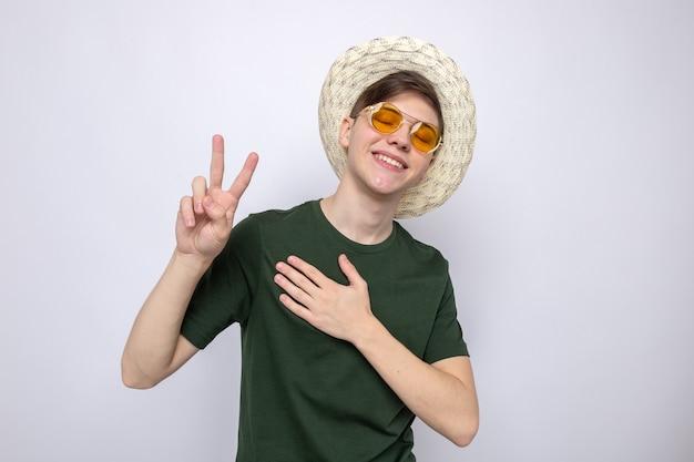 帽子と眼鏡をかけている平和ジェスチャー若いハンサムな男を示す目を閉じて満足