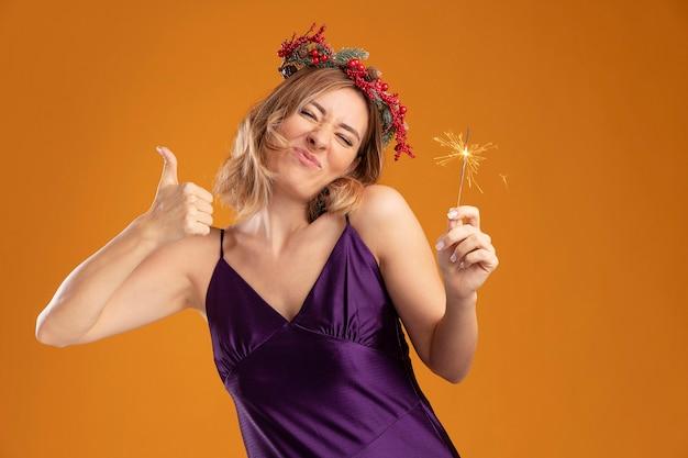 Довольная закрытыми глазами склоняет голову молодая красивая девушка в фиолетовом платье с венком, держащая бенгальские огни, показывая большой палец вверх, изолированные на коричневом фоне