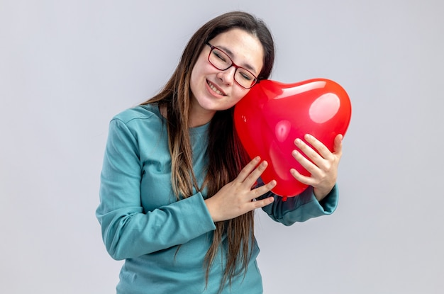 Pleased with closed eyes tilting head young girl on valentines day holding heart balloon isolated on white background