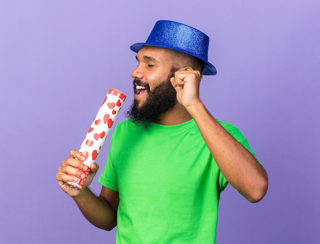 Pleased with closed eyes young afro-american guy wearing party hat holding confetti cannon sings