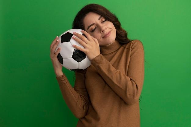 녹색 벽에 고립 된 뺨에 공을 들고 닫힌 된 눈 젊은 아름 다운 소녀에 만족