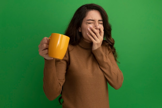 닫힌 된 눈 아름 다운 소녀 차 한잔 들고 녹색 벽에 고립 된 손으로 덮여 입에 만족