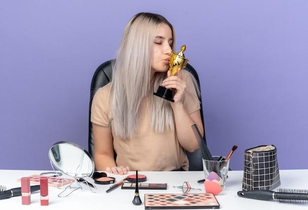 Soddisfatto degli occhi chiusi, la giovane bella ragazza si siede al tavolo con gli strumenti per il trucco che tengono e baciano la tazza del vincitore isolata sulla parete blu