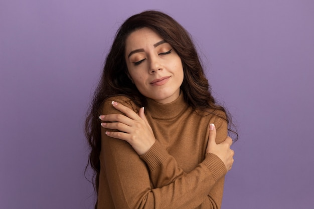 Довольная закрытыми глазами молодая красивая девушка в коричневом свитере с высоким воротом положила руки на плечо, изолированное на фиолетовой стене