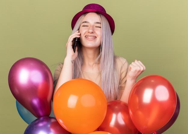 풍선 뒤에 서 있는 파티 모자와 함께 치과 교정기를 착용한 아름다운 소녀가 전화 통화를 하는 닫힌 눈에 만족합니다