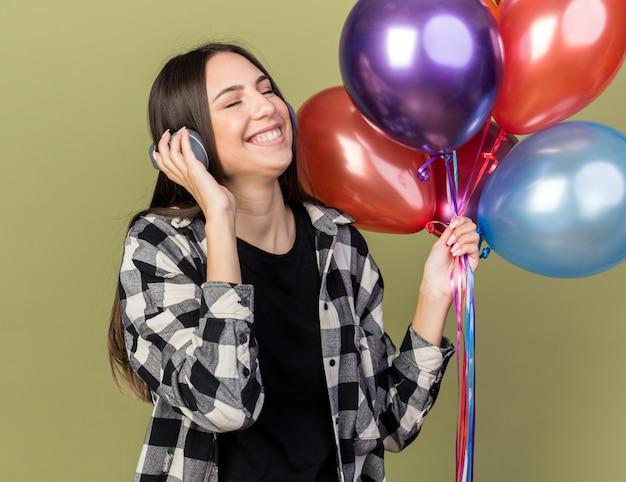 目を閉じて満足しているオリーブグリーンの壁に分離された風船を保持しているヘッドフォンを身に着けている若い美しい少女