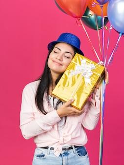 目を閉じて満足しているギフトボックスと風船を保持しているパーティーハットを身に着けている若い美しい少女