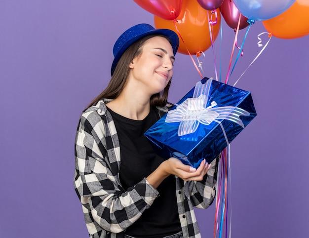 Soddisfatto degli occhi chiusi, giovane bella ragazza che indossa un cappello da festa con palloncini con scatola regalo