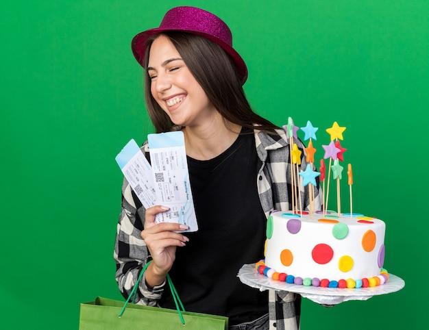 Soddisfatto degli occhi chiusi, giovane e bella ragazza che indossa un cappello da festa che tiene in mano una torta con un sacchetto regalo e biglietti isolati su una parete verde