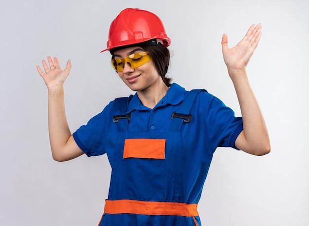 Довольный с закрытыми глазами молодая женщина-строитель в униформе и очках, поднимая руки, изолированные на белой стене