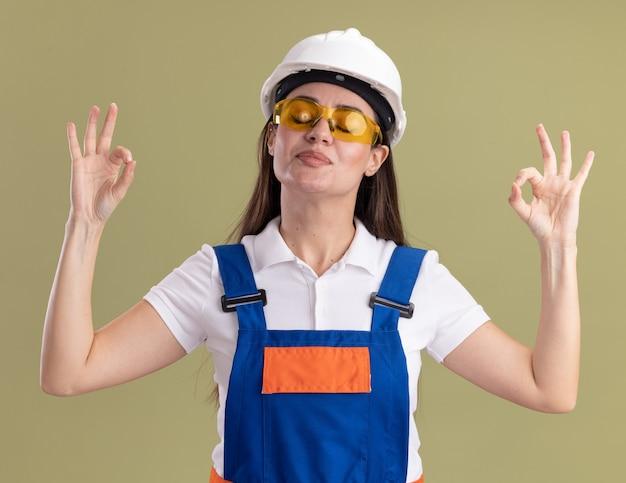 Довольная закрытыми глазами молодая женщина-строитель в униформе и очках, показывающая жест медитации, изолированная на оливково-зеленой стене