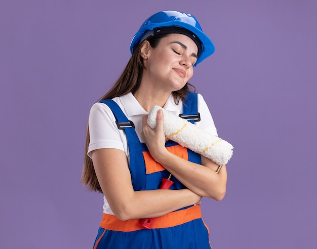 Soddisfatto degli occhi chiusi, giovane donna del costruttore in uniforme abbracciata con una spazzola a rullo isolata sul muro viola