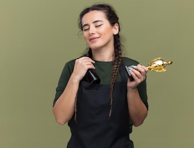 目を閉じて満足しているオリーブグリーンの壁に分離されたバリカンと勝者カップを保持している制服を着た若い女性の理髪師