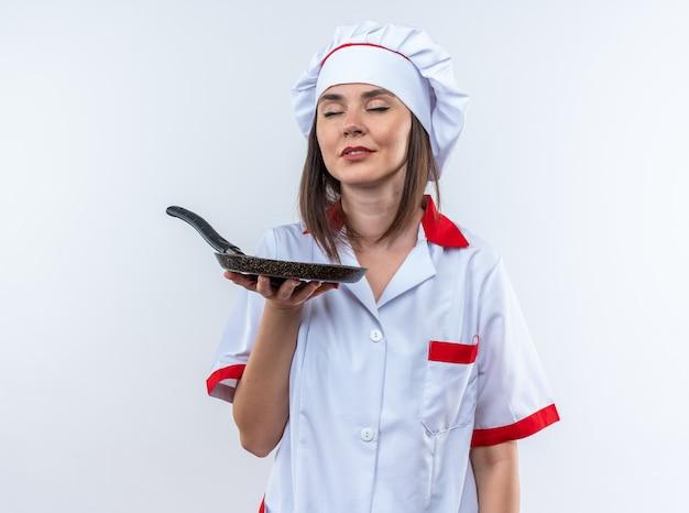 目を閉じて満足している白い壁に分離されたフライパンを保持しているシェフの制服を着た若い女性料理人