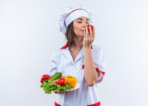 目を閉じて満足している若い女性料理人は、白い壁に隔離された彼女の手でトマトを嗅ぐプレートに野菜を持っているシェフの制服を着ています