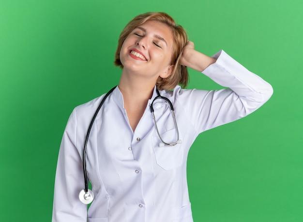 緑の壁に隔離された頭に手を置く聴診器で医療ローブを身に着けている目を閉じて満足している若い女性医師