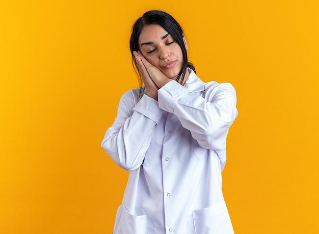 노란색 벽에 고립 된 수면 제스처를 보여주는 청진 기 의료 가운을 입고 닫힌 된 눈 젊은 여성 의사에 만족