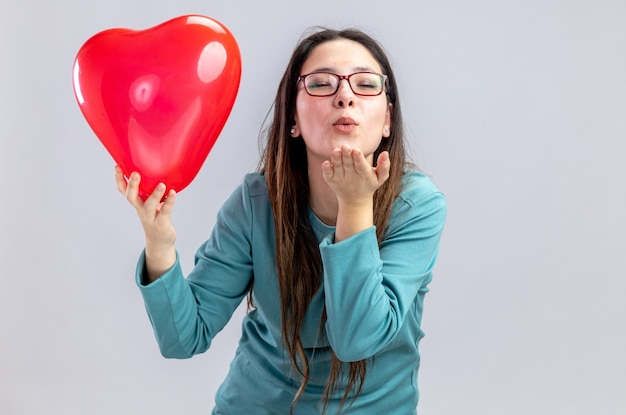 Pleased with closed eyes young girl on valentines day holding heart balloon showing kiss gesture isolated on white background