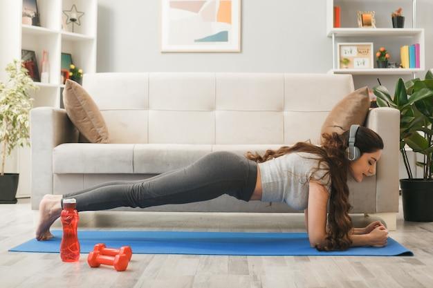 リビングルームのソファの前でヨガマットの上で運動しているヘッドフォンを身に着けている目を閉じて満足している