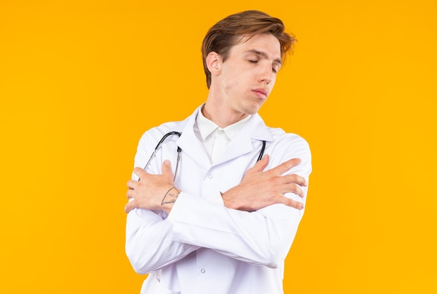 オレンジ色の壁に分離された聴診器と医療ローブを身に着けている目を閉じて若い男性医師に満足