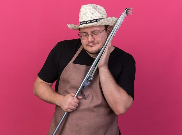 분홍색 벽에 고립 된 뺨에 잎 갈퀴를 들고 원예 모자를 쓰고 눈을 감고 젊은 남성 정원사에 만족